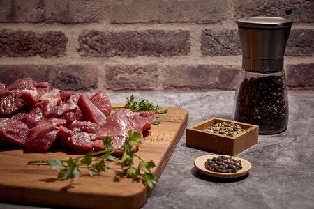 pieces of red veal meat on a wooden board and next to different spices. Stock Photo