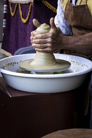 Man hands of an ancient potter creating a piece of clay