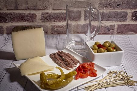 cheese board with anchovies and chilli peppers and olives next to beer mug