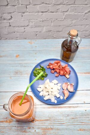 view of a fresh pitcher of red gazpacho next to its ingredients and an oil jar