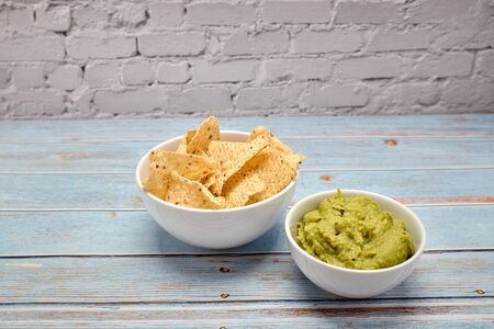 view of a bowl with spicy guacamole next to a bowl of nachos on a blue wooden table