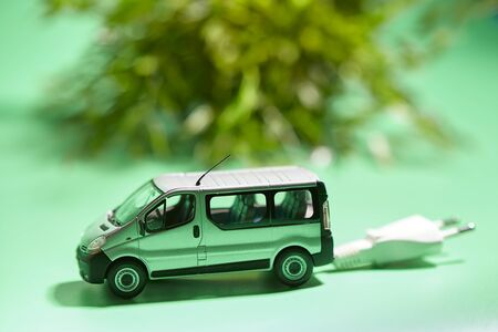 miniature of a vehicle with electric plug next to a plant on a green background 写真素材