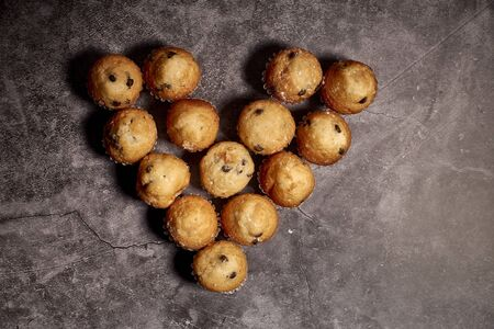 group of delicious muffins with chocolate in the shape of heart