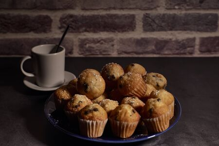 group of muffins with chocolate on a blue plate next to a cup of milk