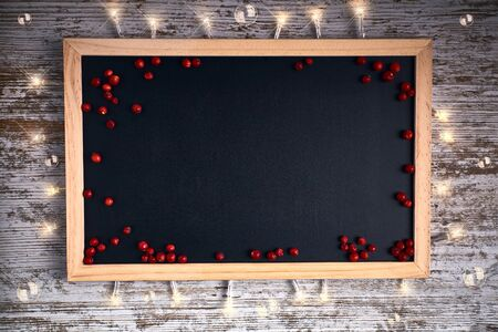 black chalkboard with small red berries and lights with space to put text