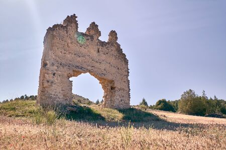 view of some old ruins of a house in the middle of a dry yellow field Imagens