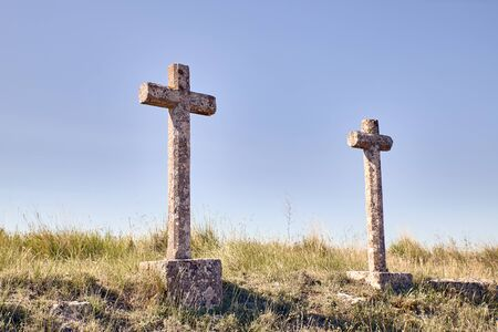 view of two crosses carved in stone in the countryside