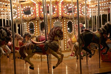 Horses on a merry-go-round with lights on a Christmas night - Party concept Stock Photo