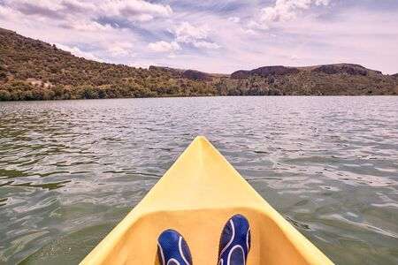 View of a mans feet while kayaking on the river on a sunny day 写真素材