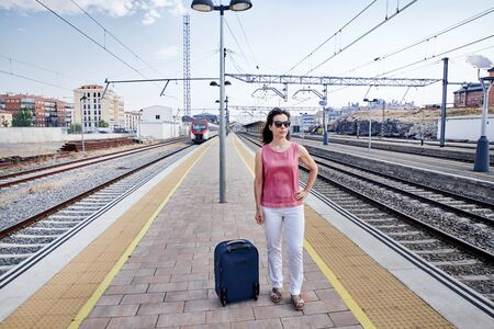 Traveler woman walking and waits train on railway platform. Concept of travel