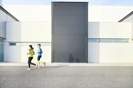 man and woman running alongside a modern building. concept sport. concept lifestyle