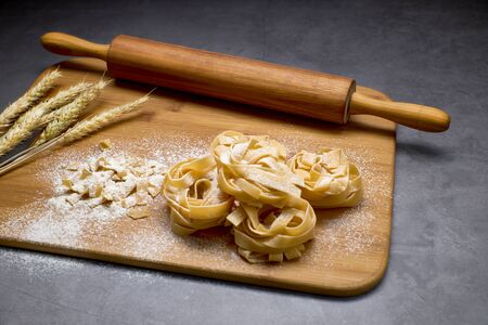Italian pasta on a board with a wood kneader. Food concept