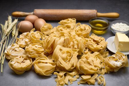 Italian pasta with some eggs, oil, flour, wood kneader and wheat. Concept of food