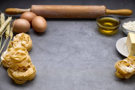 Italian pasta with some eggs, oil, flour, wood kneader and wheat. Concept of food Banque d'images
