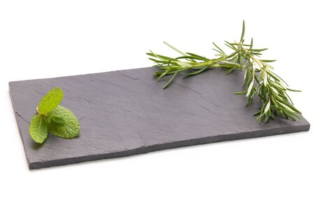 Fresh rosemary herb on a slate board with a white background 写真素材