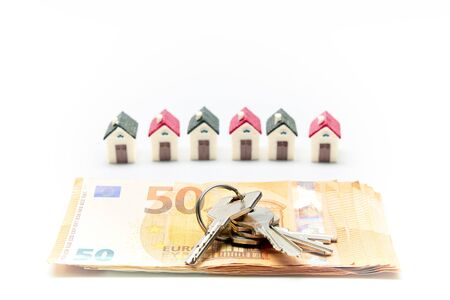Miniature homes with keys on several Euro banknotes. Sales concept, business.
