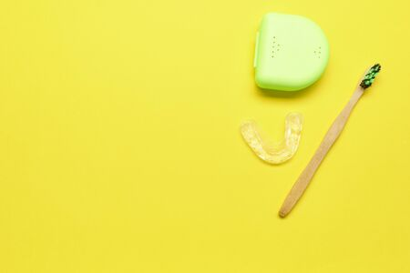Ecological toothbrush and dental aligner with its box on a yellow background. Dental care concept.