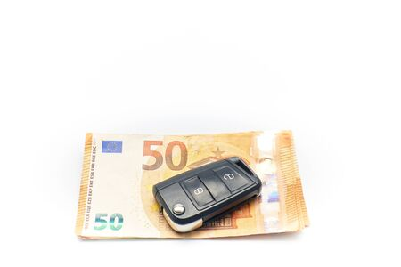 Car key and Euro bills on white background with shallow depth of field. Sales concept, automobile