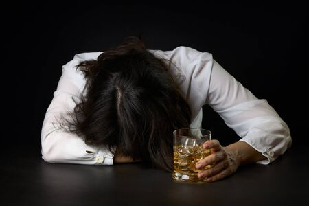 Woman who has abused alcohol with a glass of Scotch and ice. Concept of social problems