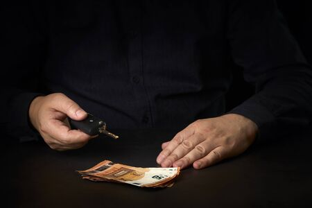 Sales agent with a car key and money on the table. Concept car sale, car renting