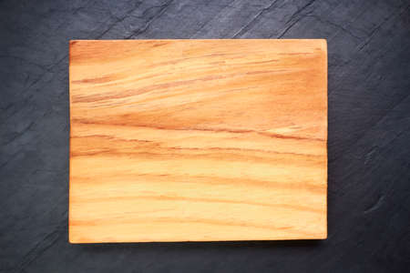 Brown wooden cutting board on black slate. Wood texture