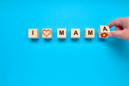 Person placing wooden cubes with a heart, flower and the words I and MAMA.