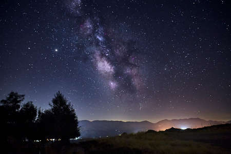 View of the Milky Way over the lights of a mountain village. Concept science, astronomy Stock Photo