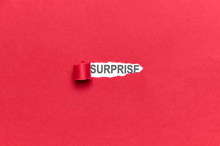 Red broken paper background with the word SURPRISE. Concept emotion, backgrounds Standard-Bild