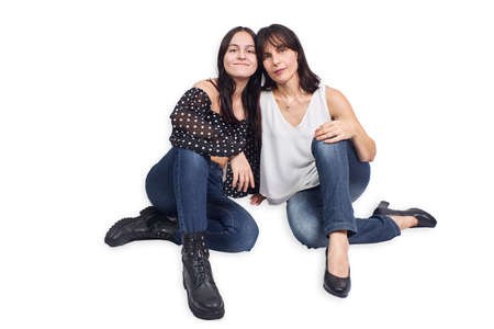 Mother and teenage daughter with their puppy on a white background Stock Photo