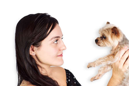 Hispanic teenage woman with small dog on white background. Pets and love concept