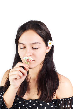 Teenage woman playing with a daisy on a white background. Fun concept