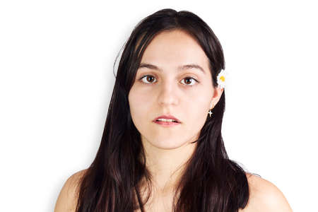 Portrait d of a teenage woman with a daisy in her hair on a white background. Youth concept