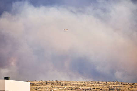 Hydroplane amidst ash clouds working to extinguish a forest fire. Natural disaster concept