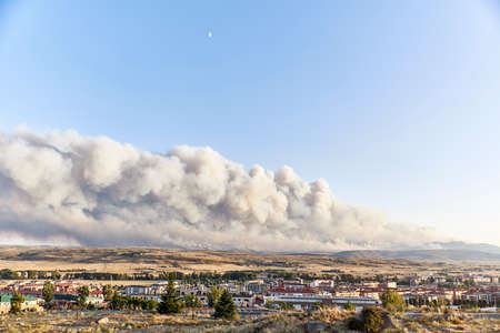 Photograph of a large forest fire with a large column of smoke on a hillside near a city. Natural disaster concept Stock Photo