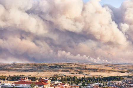 Dark and dense smoke clouds from a fire in Spain. Close-up of a large smoke cloud in the sky from a forest fire, air pollution.