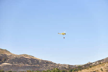 A firefighting helicopter collects water at a dam and flies into the Sierra to extinguish a forest fire. Fire concept Stock Photo