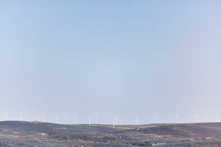 View of a burned landscape with wind turbines and the moon. climate change concept