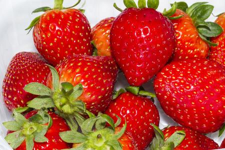monton de fresas maduras en mesa blanca