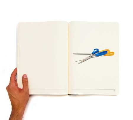 Hand holding white book with scissors inside  photo