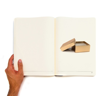 Hand holding white book with open plastic box inside  photo