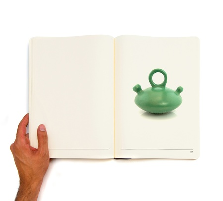 Hand holding white book with old green ceramic jar inside  photo