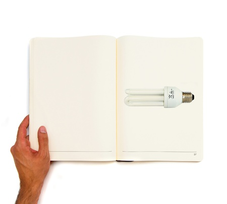 Hand holding white book with bulb inside Stock Photo - 22141311