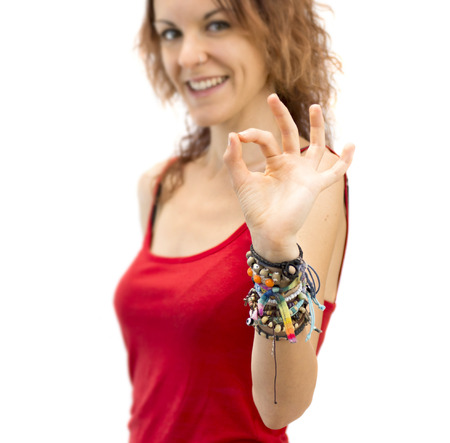 Beautiful young girl doing an OK gesture on white background photo