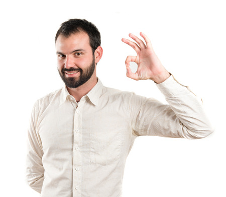 Young man doing the ok sign over white background photo