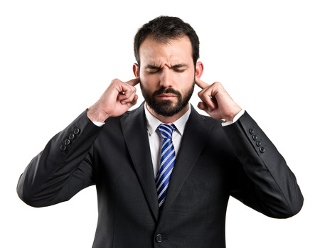 business man covering her ears over white background  photo