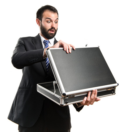 Young businessman open his briefcase over white background photo