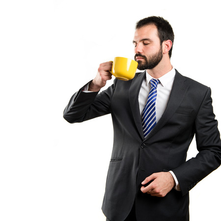 Young businessman drinking a coffee over white background photo