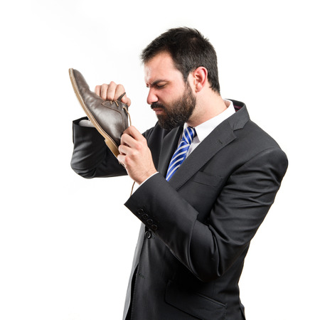 awful: Young businessmen smelling his shoes over isolated background.