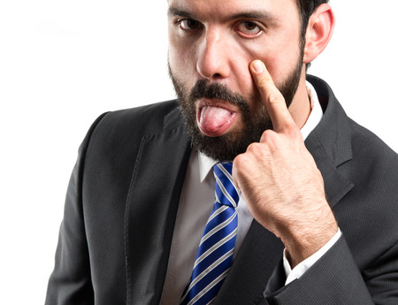 antagonistic: Young businessman making a mockery over white background  Stock Photo