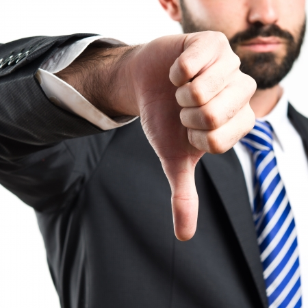 Young businessman with his thumb down over white background  Standard-Bild